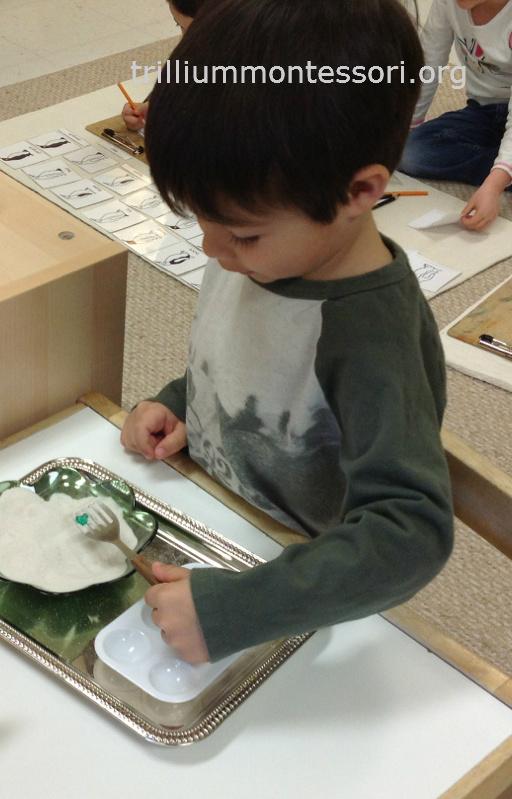 Sifting with slotted spatula- Trillium Montessori