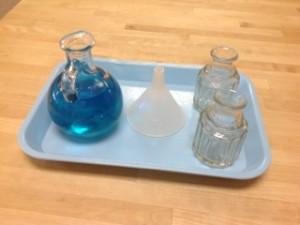 Pouring with a funnel- Montessori fine motor winter