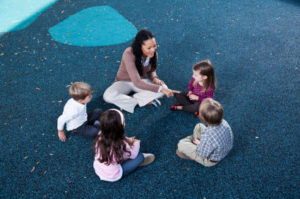 Preschoolers sitting in circle with teacher